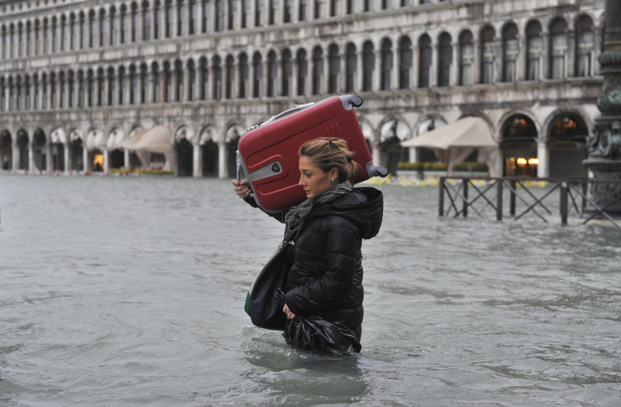 A tourist crosses flooded St. Mark's Square in Venice, Italy, Sunday, Nov. 11, 2012. High tides have flooded Venice, leading Venetians and tourists to don high boots and use wooden walkways to cross St. Mark's Square and other areas under water. Flooding is common this time of year and Sunday's level that reached a peak of 58.66 inches (149 centimeters) was below the 63 inches (160 centimeters) recorded four years ago in the worst flooding in decades. (AP Photo/Luigi Costantini)