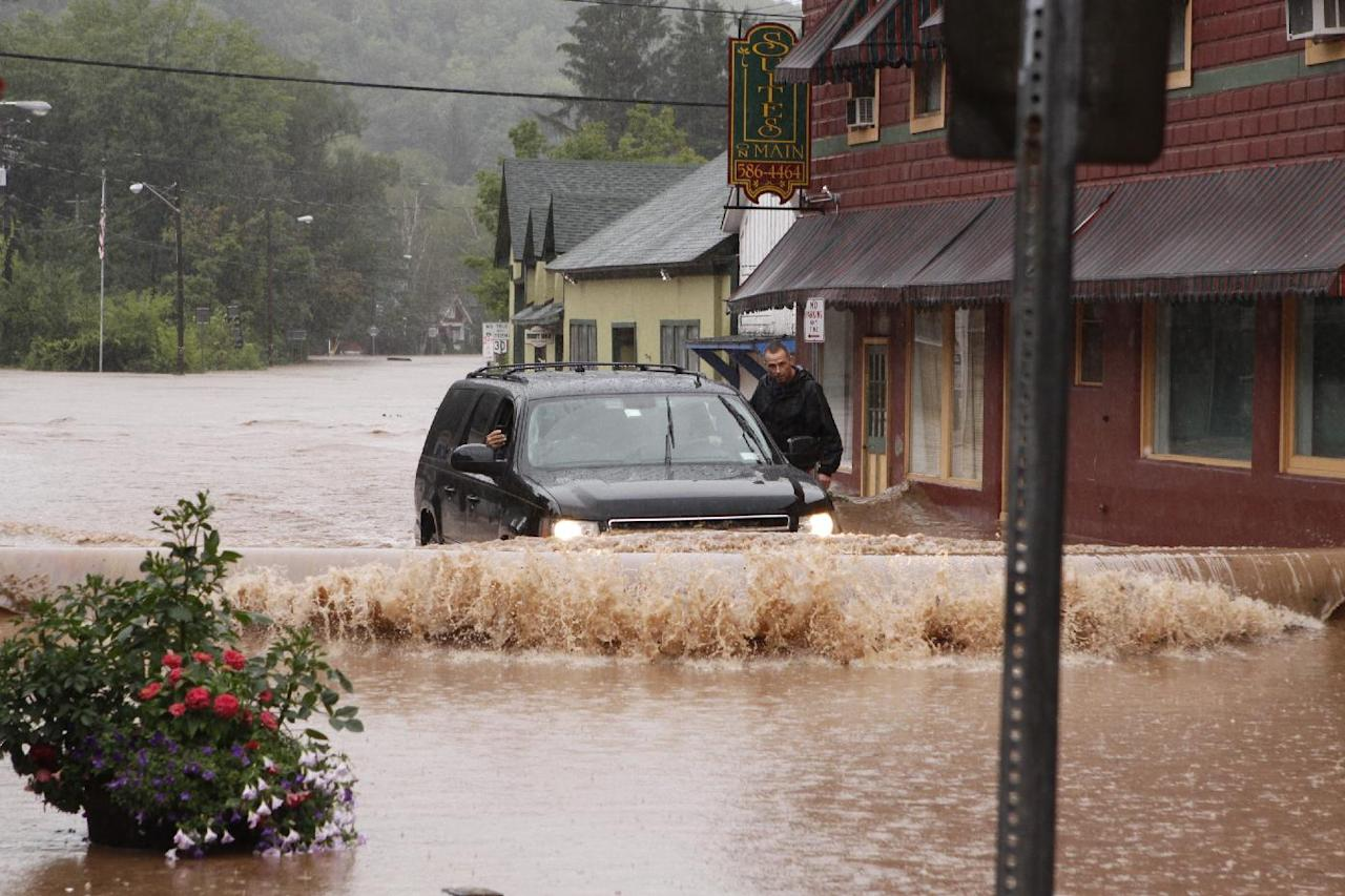 A security guard hangs on the door of Gov. Andrew Cuomo's SUV in the middle of a flooded street Sunday, Aug. 28, 2011, in Margaretville, N.Y. Gov. Cuomo was riding in the SUV, and posted some photos of the heavy flooding on his flickr site. Torrential rains from Tropical Storm Irene forced hundreds in the Hudson Valley from their homes, caused widespread power outages, closed 137 miles of the state's main highway and swelled creeks and rivers to previously unseen levels. (AP Photo/Dick Sanford)