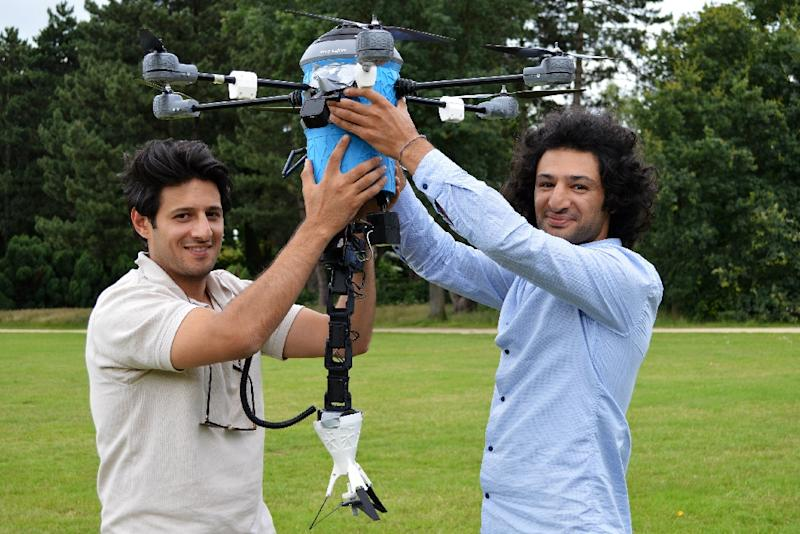 Former refugees Mahmud (L) and Massoud Hassani hold their latest invention: a low-cost drone that detects and destroys landmines (AFP Photo/Jan Hennop)