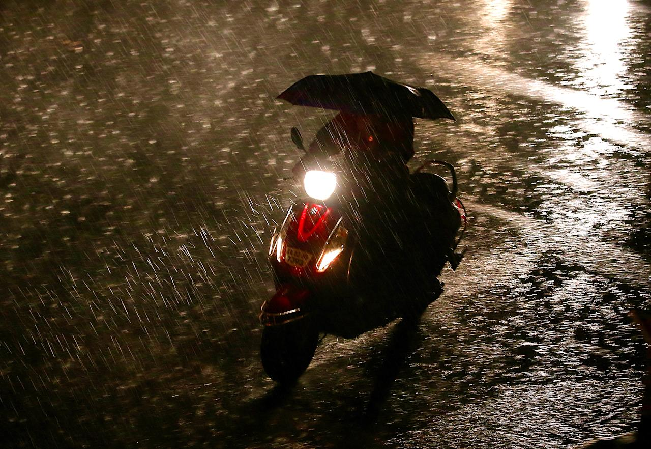 <p>An Indian motorist rides a scooter under an umbrella during an evening shower in Bangalore, India, May 26, 2017. India is expecting early winter monsoon rainfalls in the month of May. (Photo: Jagadeesh Nv/EPA) </p>