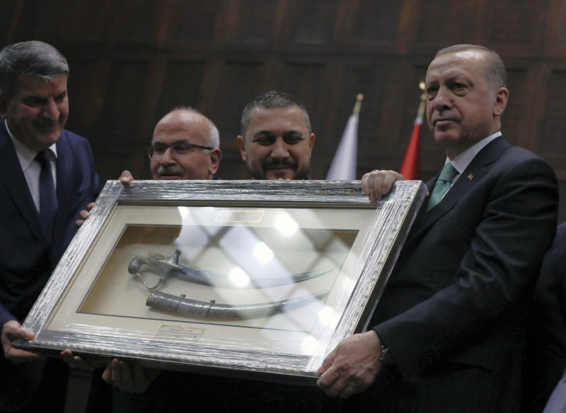 """Turkey's President and leader of ruling Justice and Development Party Recep Tayyip Erdogan, right, receives a dagger from supporters as gift as he addresses the members of his ruling party at the parliament in Ankara, Turkey, Tuesday, Feb. 13, 2018. Erdogan issued a warning Tuesday to Greece, Cyprus and international companies exploring for gas in the eastern Mediterranean not to """"step out of line"""" and encroach on Turkey's rights.(AP Photo/Burhan Ozbilici)"""
