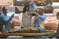 Archaeologists x-ray a mummy wrapped in a burial shroud and adorned with brightly coloured hieroglyphic pictorials, during the unveiling more than a 100 intact sarcophagi, at Egypt's Saqqara necropolis on November 14, 2020