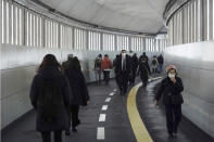 People wearing protective masks to help curb the spread of the coronavirus walk along an underpass Tuesday, Jan. 26, 2021, in Tokyo. The Japanese capital confirmed more than 1000 new coronavirus cases on Tuesday. (AP Photo/Eugene Hoshiko)