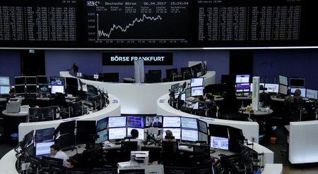 Traders work at their desks in front of the German share price index, DAX board, at the stock exchange in Frankfurt, Germany, April 6, 2017. REUTERS/Staff/Remote