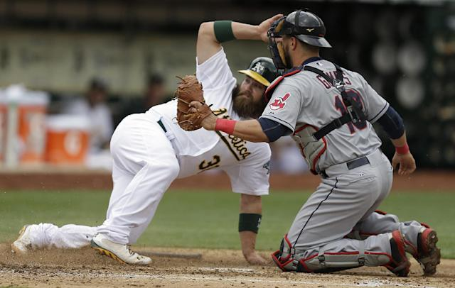 Cleveland Indians catcher Yan Gomes, right, tags out Oakland Athletics' Derek Norris in the second inning of a baseball game on Wednesday, April 2, 2014, in Oakland, Calif. (AP Photo/Ben Margot)