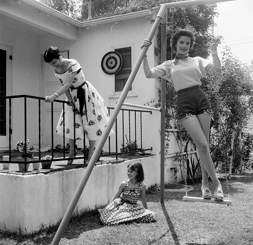 "<p>Wood, seen here at her Los Angeles home with her mother, Maria Zakharenko, and younger sister, had a <a href=""https://www.cnn.com/2011/11/19/showbiz/celebrity-news-gossip/natalie-wood-life/index.html"" rel=""nofollow noopener"" target=""_blank"" data-ylk=""slk:complicated relationship"" class=""link rapid-noclick-resp"">complicated relationship</a> with her mother, who managed her career. An aspiring performer herself, Maria reportedly <a href=""https://www.newsweek.com/real-tragedy-natalie-wood-65945?utm_medium=google"" rel=""nofollow noopener"" target=""_blank"" data-ylk=""slk:pushed her daughters"" class=""link rapid-noclick-resp"">pushed her daughters</a> into the industry and was <a href=""https://variety.com/2001/more/reviews/natasha-the-biography-of-natalie-wood-1200469640/"" rel=""nofollow noopener"" target=""_blank"" data-ylk=""slk:extremely controlling over their careers"" class=""link rapid-noclick-resp"">extremely controlling over their careers</a>. </p>"