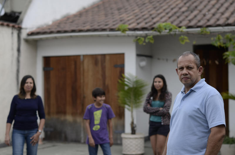 """In this Tuesday, June 25, 2013 photo, Paulo Cavalcante, 49, right, Adela, his wife of 16 years, left, their 15-year-old daughter Maria and 10-year-old son Antonio, pose for a photo at their home in the Rio de Janeiro suburb of Iraja, Brazil. """"We're among the fortunate ones and we're suffering,"""" said the 49-year-old, a public servant with Rio's City Hall. """"We've been completely abandoned by our government."""" (AP Photo/Nicolas Tanner)"""