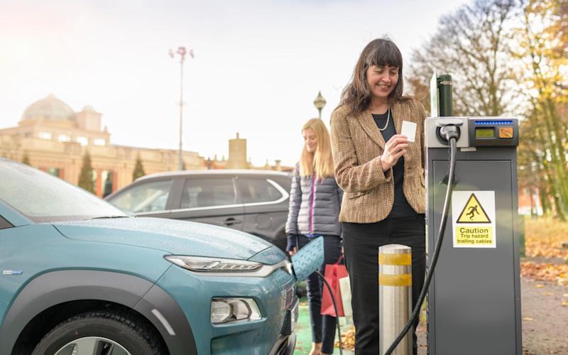 Female shoppers charging electric car at charge point, Manchester, UK - Cultura Creative / Alamy