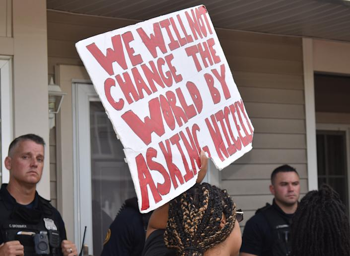 A protester holds a sign at an anti-racism demonstration at the house of a bias-crimes suspect in Mount Laurel.
