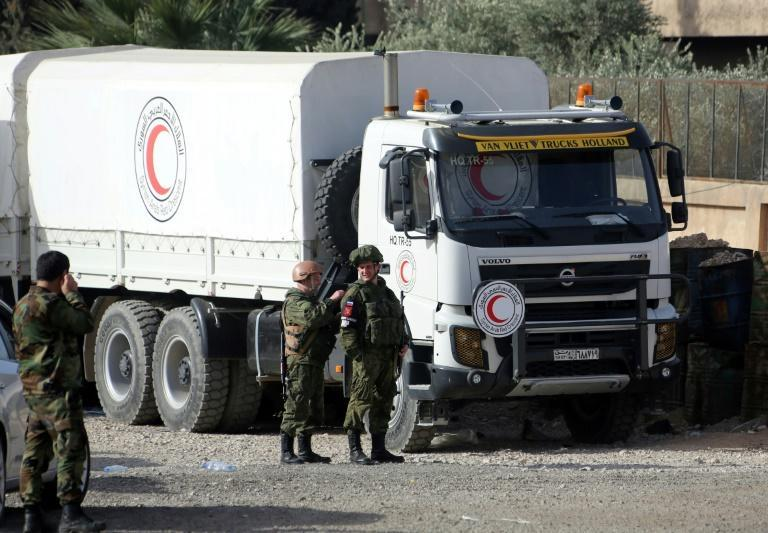 Russian soldiers stand beside an aid truck waiting at the Al-Wafideen checkpoint on March 8, 2018 to pass from Syrian government-held territory into the rebel enclave of Eastern Ghouta