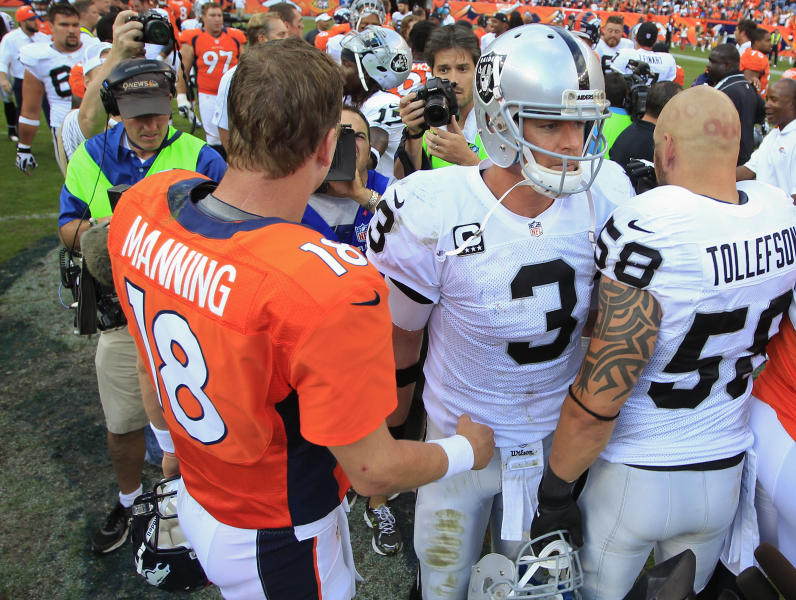 Denver Broncos quarterback Peyton Manning (18) talks with Oakland Raiders quarterback Carson Palmer (3) after playing in an NFL football game, Sunday, Sept. 30, 2012, in Denver. The Broncos won 37-6. (AP Photo/David Zalubowski)