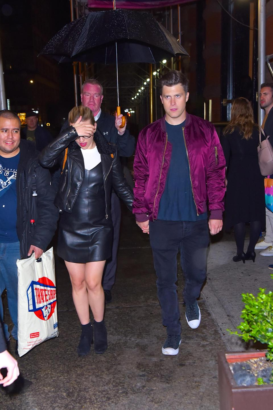 johansson shielding her face while walking hand in hand with jost