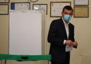 Georgia's Prime Minister Gakharia holds a ballot before casting his vote during a parliamentary election in Tbilisi