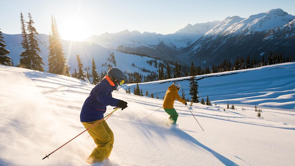 Couple skiing on a sunny powder day.
