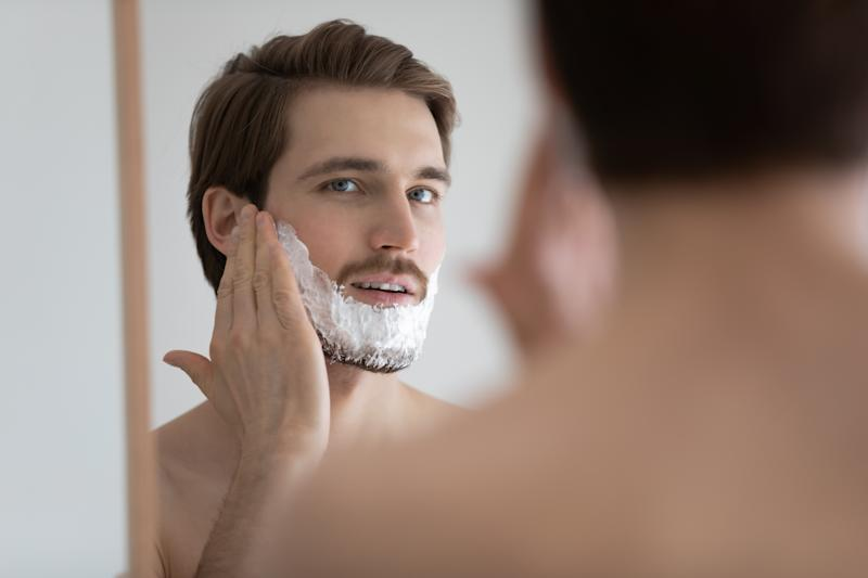 Young caucasian man look in mirror in bathroom apply foam shaving after shower, millennial male do beauty skin procedures, take care of bristle beard in bath, skincare body hygiene concept