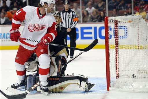 Detroit Red Wings right wing Daniel Cleary, left, deflects a shot for a goal past Anaheim Ducks goalie Jonas Hiller, of Switzerland, during the first period of their NHL hockey game, Sunday, March 24, 2013, in Anaheim, Calif. (AP Photo/Mark J. Terrill)