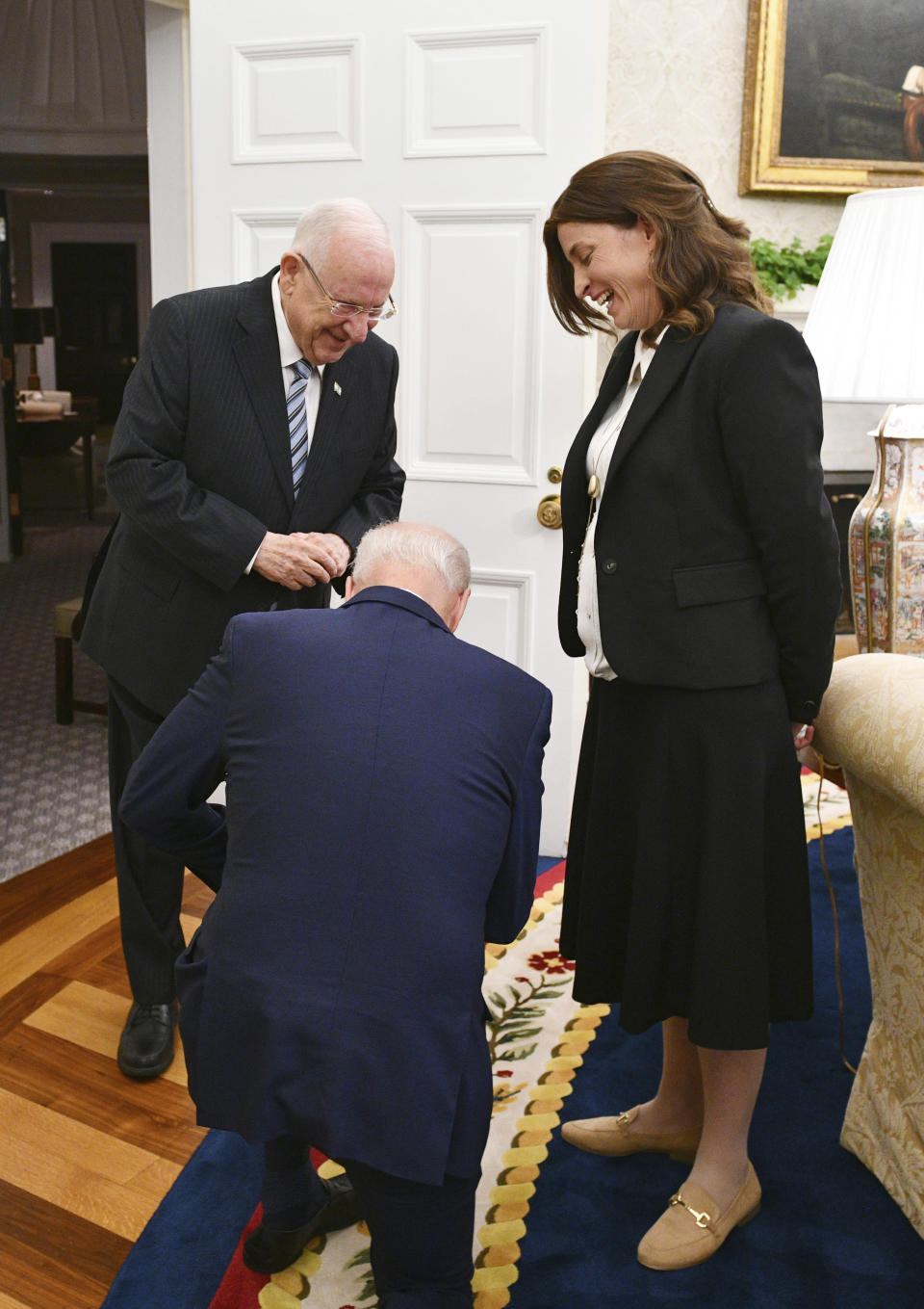 """In this June 28, 2021 photo provided by the Israeli Government Press Office, President Joe Biden, center, meets with Israel President Reuven Rivli, left, and Rivka Ravitz, head of Rivli's delegation, in the White House in Washington. On Friday, July 9, 2021, The Associated Press reported on stories circulating online incorrectly asserting Biden was kneeling down to the Israeli president, """"pledging unconditional support to Israel."""" But Haim Zach, a press photographer for the Israeli government, said Biden knelt after learning Ravitz was the mother of 12, saying as a Catholic man he wanted to show his admiration. (Haim Zach/GPO via AP)"""