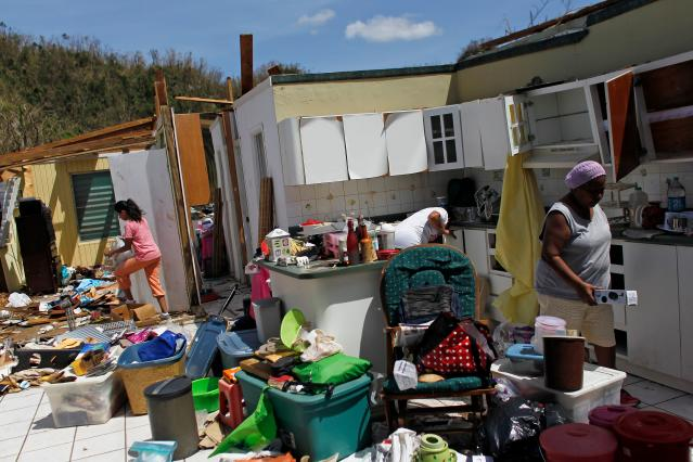 <p>Family members collect belongings after hurricane force winds destroyed their house in Toa Baja, west of San Juan, Puerto Rico, on Sept. 24, 2017 following the passage of Hurricane Maria.<br> Authorities in Puerto Rico rushed on September 23, 2017 to evacuate people living downriver from a dam said to be in danger of collapsing because of flooding from Hurricane Maria. (Photo: Ricardo Arduengo/AFP/Getty Images) </p>