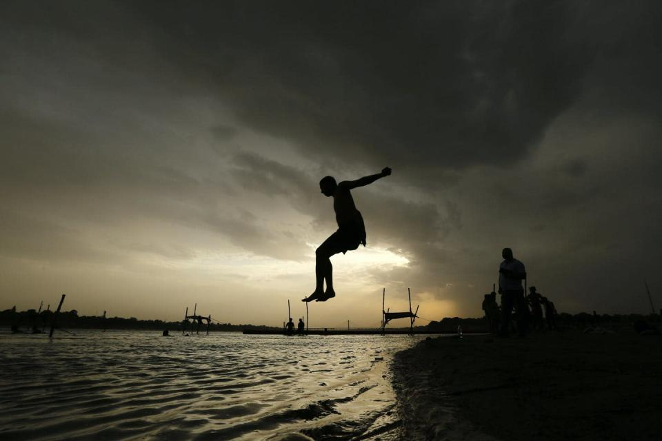 Boy mid-air above a river at sunset