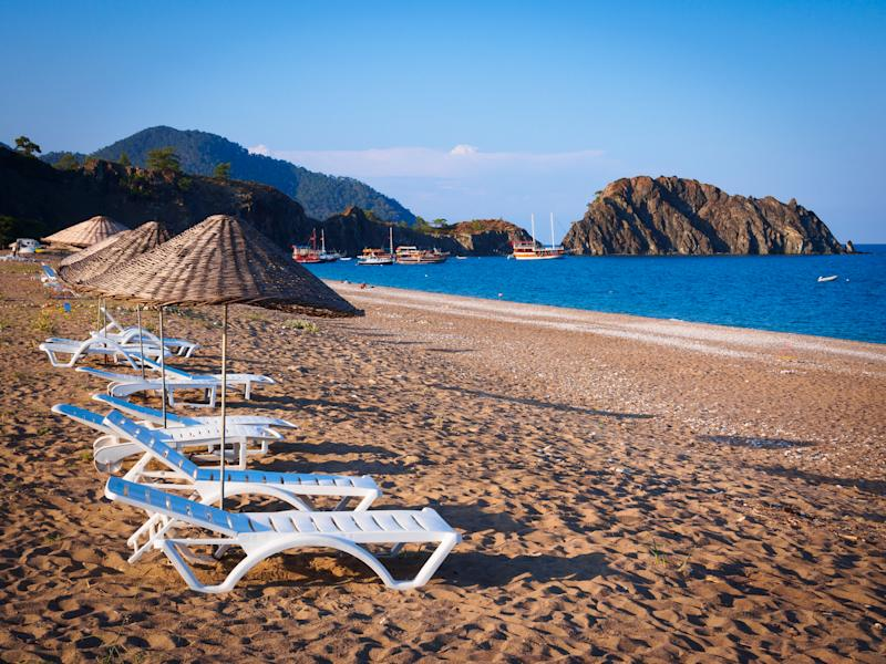 Lounge chairs and woven cane umbrellas on a white sandy beach in Cirali, Turkey