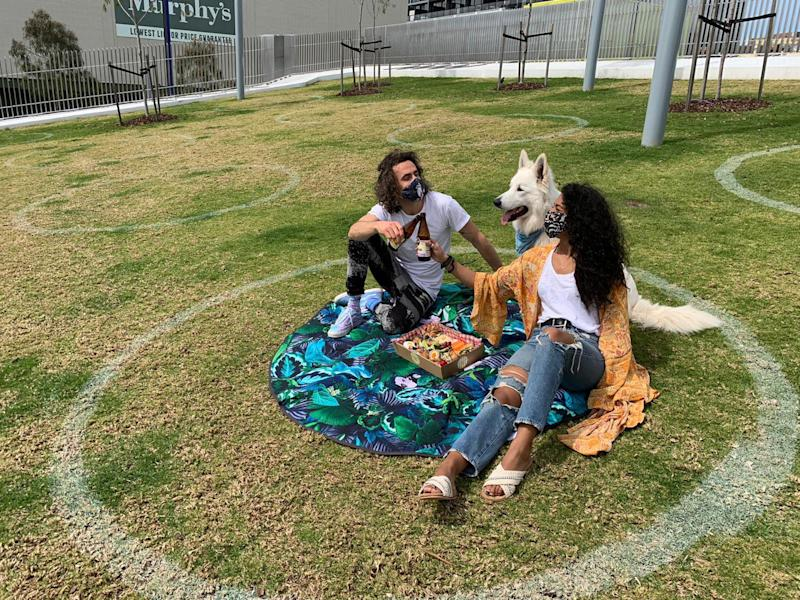 Pictured are two people and a dog sitting in one of the circles in the Chapel St Precinct.