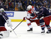 Carolina Hurricanes' Zach Boychuk (22) takes a shot between Columbus Blue Jackets goalie Curtis McElhinney (30) and Blue Jackets' Tim Erixon (20) during the first period of an NHL hockey game in Columbus, Ohio, Tuesday, Nov. 4, 2014. Boychuk scored on the play. (AP Photo/Paul Vernon)