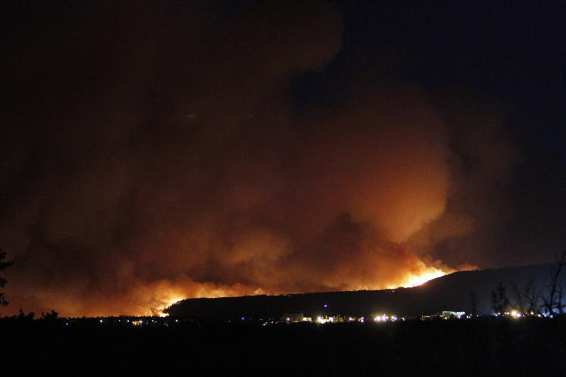 A wildfire crests over the hills above Los Alamos National Labs Sunday June 26, 2011 in New Mexico.  A fast-moving wildfire forced officials at the Los Alamos National Laboratory to close the site Monday.  (AP Photo/Luis Sánchez Saturno/The New Mexican)