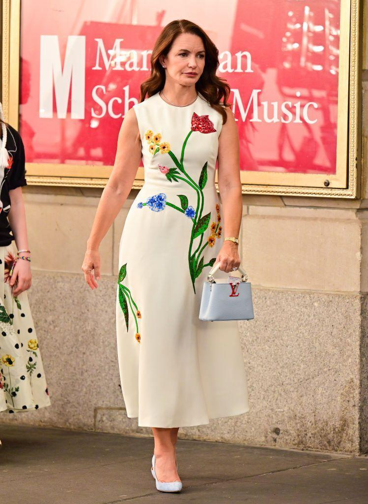 """<p>Charlotte Goldenblatt-York looks very ready to attend whatever event at the Manhattan School of Music that the best friends are attending. </p><p>Wearing a dress by Texas-born bridal designer, Lela Rose Bridal, the outfit is accessorised with a <a href=""""https://uk.louisvuitton.com/eng-gb/products/capucines-mini-capucines-nvprod2250020v"""" rel=""""nofollow noopener"""" target=""""_blank"""" data-ylk=""""slk:light blue Louis Vuitton mini bag"""" class=""""link rapid-noclick-resp"""">light blue Louis Vuitton mini bag</a> and Manolo Blahnik BB pumps in light grey.</p><p><a class=""""link rapid-noclick-resp"""" href=""""https://go.redirectingat.com?id=127X1599956&url=https%3A%2F%2Fwww.net-a-porter.com%2Fen-gb%2Fshop%2Fproduct%2Fmanolo-blahnik%2Fbb-90-suede-pumps%2F1333133&sref=https%3A%2F%2Fwww.elle.com%2Fuk%2Ffashion%2Fcelebrity-style%2Fg37021459%2Fand-just-like-that-style-fashion%2F"""" rel=""""nofollow noopener"""" target=""""_blank"""" data-ylk=""""slk:SHOP NOW"""">SHOP NOW </a> Manolo Blahnik BB 90 pumps in cream, £515</p>"""
