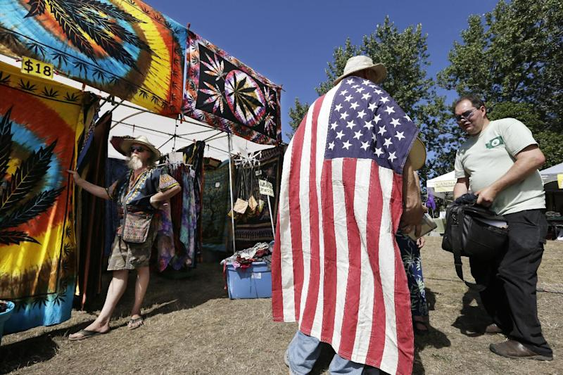 FILE -- In this Aug. 16, 2013 file photo, a man wears an American flag as he walks past a vendor selling tie-dyed products at the first day of Hempfest in Seattle. One of the U.S. Justice Department's top concerns in allowing Washington and Colorado to move forward with plans to legalize and tax marijuana sales is seeing that the states keep criminals out of the industry. But the DOJ itself is refusing to let Washington run national background checks on those applying to run legal pot businesses, The Associated Press has learned, and those who have received the first legal pot licenses have done so without going through a national background check. (AP Photo/Elaine Thompson, File)