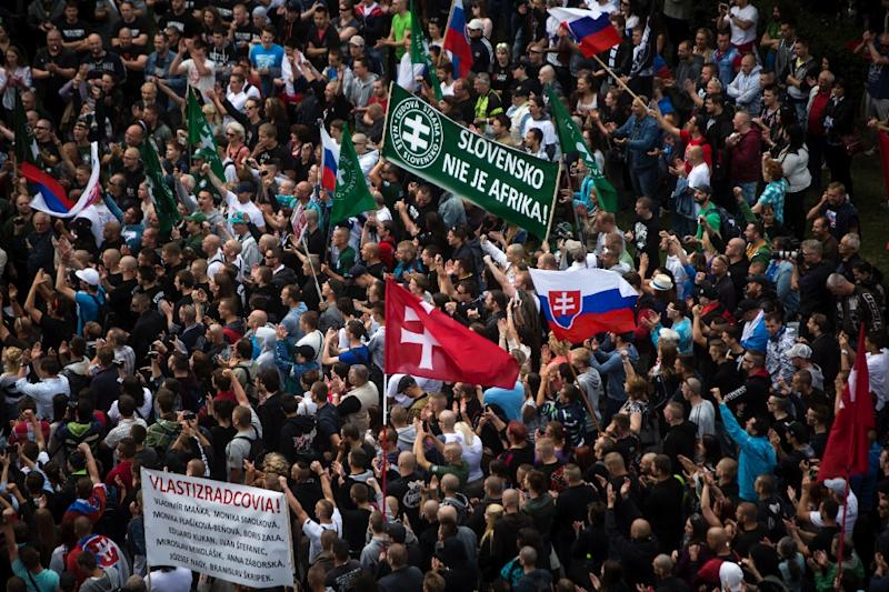 "Participants wave flags and hold a banner reading ""Slovakia is not Africa"" during an anti-immigration rally on June 20, 2015 in Bratislava, Slovakia (AFP Photo/Vladimir Simicek)"