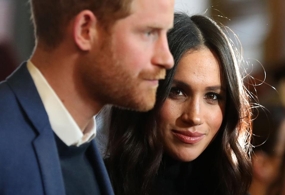 """File photo dated 13/02/18 of the Duke and Duchess of Sussex during a reception for young people at the Palace of Holyroodhouse, in Edinburgh. The Duchess of Sussex has returned to Canada as the Queen and other senior royals took decisive action and ordered their teams to find a """"workable solution"""" to Harry and Meghan's future roles."""