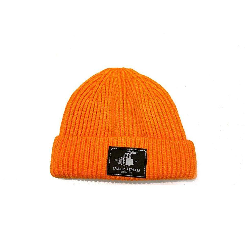 """<p><strong>PERALTA PROJECT</strong></p><p>peraltaproject.com</p><p><strong>$25.00</strong></p><p><a href=""""https://peraltaproject.com/collections/hats/products/taller-peralta-union-beanie"""" rel=""""nofollow noopener"""" target=""""_blank"""" data-ylk=""""slk:Shop Now"""" class=""""link rapid-noclick-resp"""">Shop Now</a></p><p>No fall wardrobe would be complete without a beanie. Our selection for this year is the Taller Peralta beanie, named after the flagship store and studio of contemporary artist M. Tony Peralta, fashioned in his signature vibrant orange. Peralta is known for his """"Rolos and Icons"""" paintings, consisting of iconic Latinas (including Frida Kahlo, Selena Quintanilla, and even Dora The Explorer) rocking a set of rolos. Earlier this year, Peralta made headlines when reprised the series with """"Enfermera Con Rolos,"""" depicting health care workers on the front lines of this pandemic. </p>"""