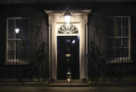 A candle lit by Britain's Prime Minister Boris Johnson and his fiancee Carrie Symonds placed on the doorstep of 10 Downing Street, London, during a doorstep vigil for Sarah Everard, Saturday, March 13, 2021. A serving British police officer accused of the kidnap and murder of a woman in London has appeared in court for the first time. Wayne Couzens, 48, is charged with kidnapping and killing 33-year-old Sarah Everard, who went missing while walking home from a friend's apartment in south London on March 3. (Aaron Chown/PA via AP)