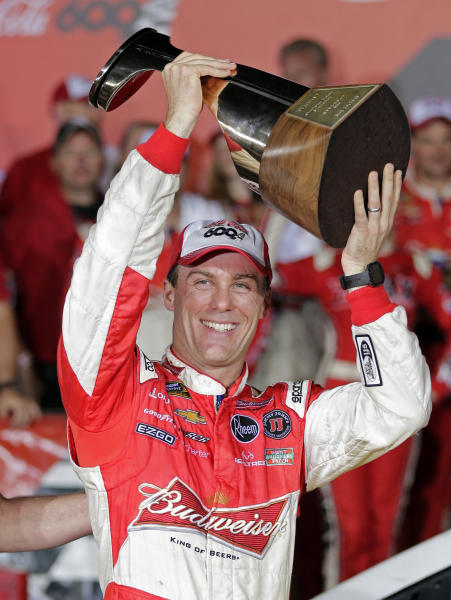 Kevin Harvick raises the trophy in victory lane after winning the NASCAR Sprint Cup series Coca-Cola 600 auto race at Charlotte Motor Speedway in Concord, N.C., Sunday, May 26, 2013. (AP Photo/Chuck Burton)