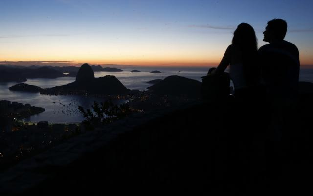 A couple is seen in front of Sugar Loaf mountain in Rio de Janeiro March 11, 2014. Rio de Janeiro is one of the host cities for the 2014 soccer World Cup in Brazil. REUTERS/Sergio Moraes (BRAZIL - Tags: SPORT SOCCER WORLD CUP)