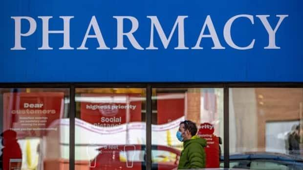 A man wearing a mask walks past a pharmacy in Ottawa earlier this month. As of April 12, around 80 additional city pharmacies will be able to vaccinate people 55 and older against COVID-19. (Mathieu Theriault/Radio-Canada - image credit)