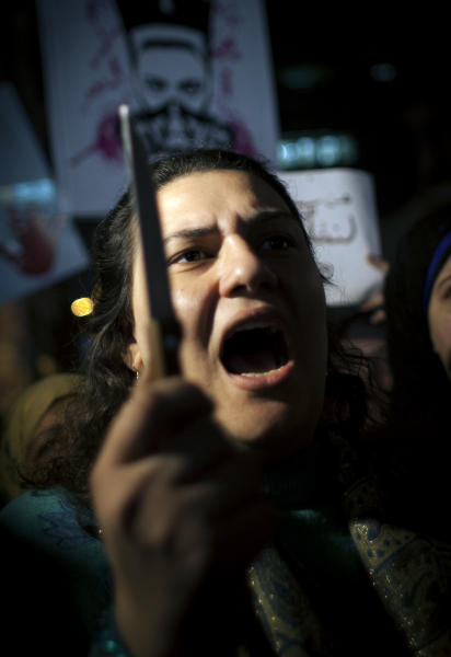A female Egyptian activist holds a knife while taking part in a protest for women against sexual harassment and against the Islamist dominated Shura Council blaming women for the attacks against them, in Cairo, Egypt, Tuesday, Feb. 12, 2013. (AP Photo/Nasser Nasser)
