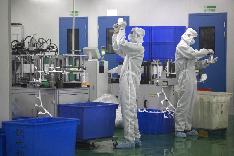 In this April 12, 2020, photo, workers inspect masks at a mask factory production line of the Wuhan Zonsen Medical Products Co. Ltd. in Wuhan in central China Hubei province. The United States, Japan and France are prodding their companies to rely less on China to make the world's smartphones, drugs and other products. But even after the coronavirus derailed global trade, few are willing to give up access to its skilled workers, vast market and efficient suppliers by moving factories closer to home.(AP Photo/Ng Han Guan)