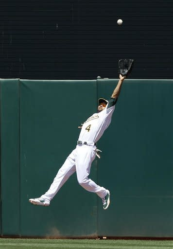 Oakland Athletics left fielder Coco Crisp catches a fly ball hit by San Diego Padres' Cameron Maybin during the fifth inning of a baseball game in Oakland, Calif., Saturday, June 16, 2012. (AP Photo/Jeff Chiu)
