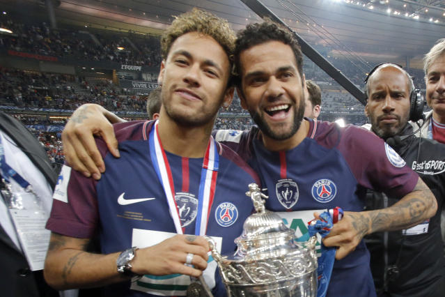 PSG's Neymar, left, and his teammate Dani Alves pose with the French Cup 2018 trophy at the Stade de France stadium in Saint-Denis, outside Paris, Tuesday, May 8, 2018. Paris Saint-Germain beat resilient third-division side Les Herbiers 2-0 to win the French Cup. (AP Photo/Michel Euler)