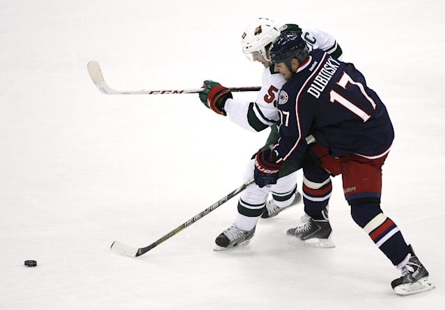 Columbus's Brandon Dubinsky (17) collides with Minnesota's Tyler Graovac (53) in the third period of their NHL preseason game, Monday Sept. 23, 2013 in Columbus, Ohio. (AP Photo/Mike Munden)