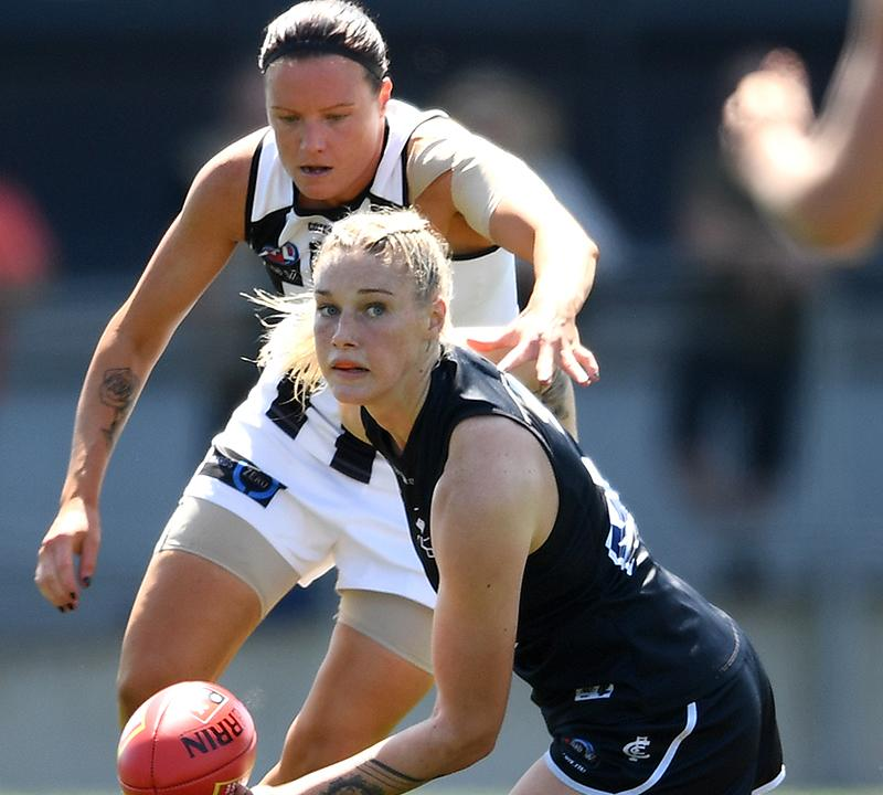 Tayla Harris, pictured here handballing while being tackled by Stacey Livingstone in the AFLW.