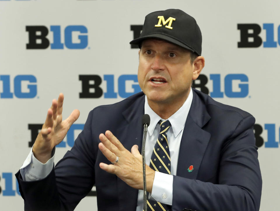 FILE - In this July 19, 2019, file photo, Michigan head coach Jim Harbaugh responds to a question during the Big Ten Conference NCAA college football media days in Chicago. Big Ten is going to give fall football a shot after all. Less than five weeks after pushing football and other fall sports to spring in the name of player safety during the pandemic, the conference changed course Wednesday, Sept. 16, 2020, and said it plans to begin its season the weekend of Oct. 23-24.(AP Photo/Charles Rex Arbogast, File)