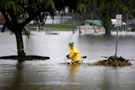 <p>A woman pushes her bicycle through flooding caused by Hurricane Lane in Hilo, Hawaii, Aug. 25, 2018. (Photo: Terray Sylvester/Reuters) </p>