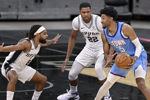 Houston Rockets' Christian Wood, right, looks to pass as he is defended by San Antonio Spurs' Rudy Gay (22) and Patty Mills during the first half of an NBA basketball game, Saturday, Jan. 16, 2021, in San Antonio. (AP Photo/Darren Abate)
