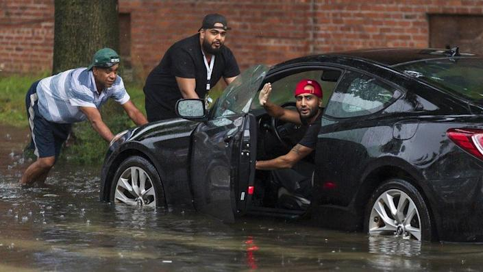 People push a car in floodwaters in New York
