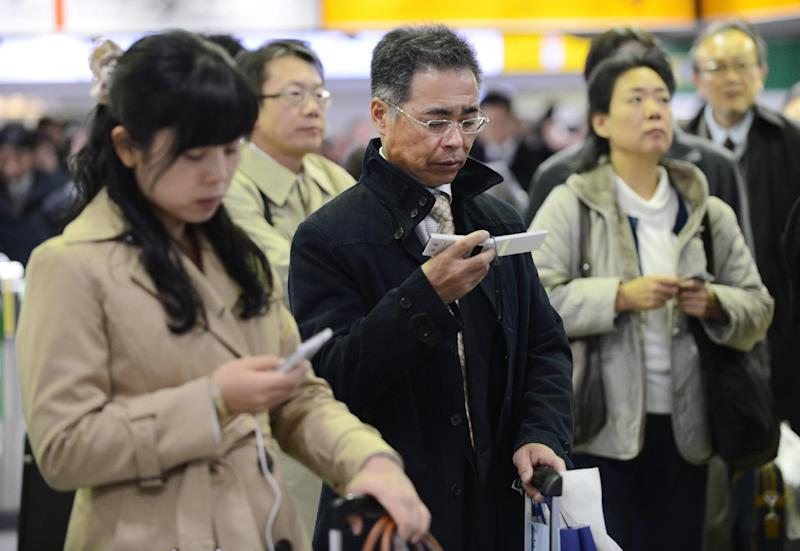 People look at their mobile phones to check updated information on possible rail line suspensions following a powerful 7.3 undersea earthquake in northern Japan at Tokyo Station on December 7, 2012 (AFP Photo/Toru Yamanaka)