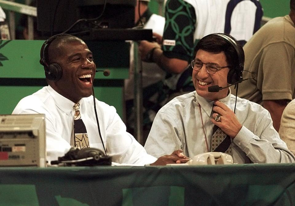 """FILE - Magic Johnson, left, shares a laugh with Marv Albert during preliminary basketball action between Brazil and Puerto Rico at the Centennial Summer Olympic Games in Atlanta, in this Saturday, July 20, 1996, file photo. Marv Albert plans to retire following the NBA's Eastern Conference finals, ending a broadcasting career that has spanned nearly 60 years. """"There is no voice more closely associated with NBA basketball than Marv Albert's,"""" NBA Commissioner Adam Silver said in a statement released Monday, May 17, 2021, by Turner Sports.(AP Photo/Elise Amendola, File)"""