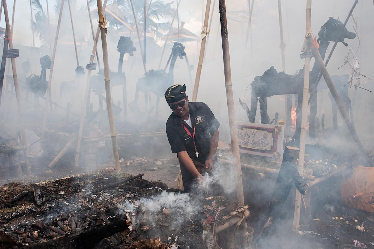 UBUD, BALI, INDONESIA - AUGUST 18: A man clears the debris of a burned sarchophagus at the cremation site during a Balinese Hindu mass cremation on August 18, 2013 in Ubud, Bali, Indonesia. More than 60 corpses were collectively cremated to share the expense of the ceremony. Well known as Ngaben, it is one of the most important ceremonies for Balinese Hindu people, as they believe it will free the spirit from the deceased body so it can reincarnate. (Photo by Putu Sayoga/Getty Images)