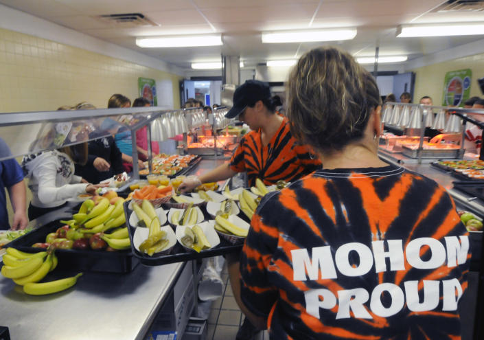 Michel Sasso, front and Maria Frisone restock food items along the lunch line of the cafeteria at Draper Middle School in Rotterdam, N.Y., Tuesday, Sept. 11, 2012. The leaner, greener school lunches served under new federal standards are getting mixed grades from students. (AP Photo/Hans Pennink)